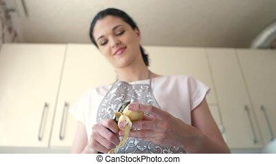 Woman peels potatoes at kitchen - Young woman peeling...