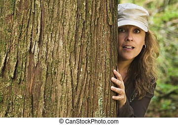 Woman peering around tree
