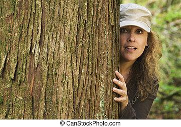 Woman peering around tree