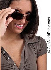 Woman peering over her sunglasses