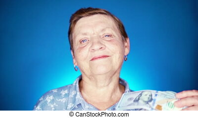 Woman pensioner on blue background with dollars. Grandmother...