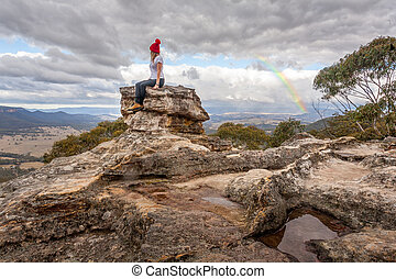 Woman perched on rock pillar peak with the best views below braving the mountain chill