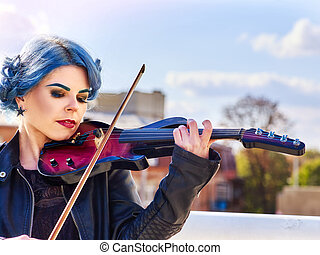 Woman perform music on violin park outdoor. Girl performing jazz.
