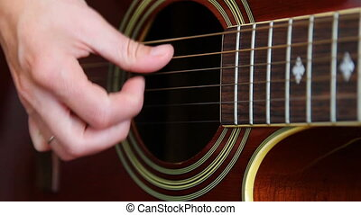 Woman performer hand play on guitar, close up