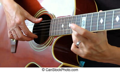 Woman performer hand play on guitar