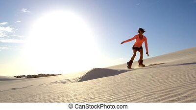 Woman performing a jump while sand boarding 4k - Woman...