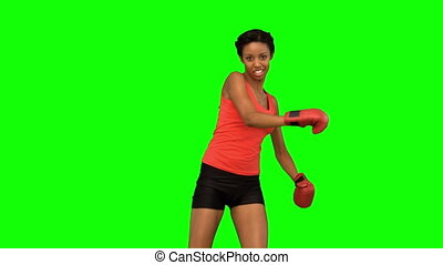 Woman performing air kick on green screen in slow motion