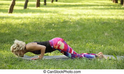 Blonde woman performing cobra asana and the dog muzzle down pose in the park