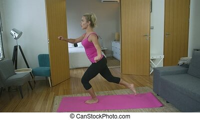 Woman performing lunges at home - Lovely young woman in...