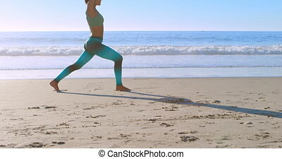 Woman performing yoga in the beach 4k - Woman performing...