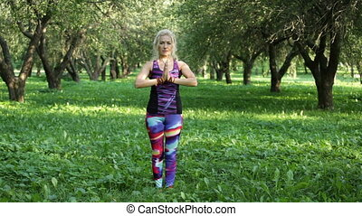 Woman performing yoga in the park - Woman performing yoga...