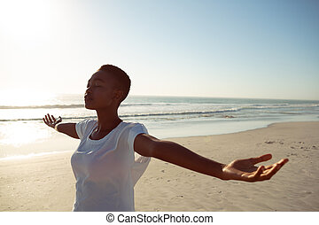 Woman performing yoga on the beach - Front view of young ...