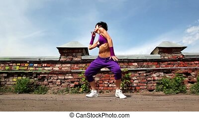 Woman performs modern dance, at background of small wall