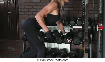 Woman performs one arm bent-over dumbbell row exercise -...