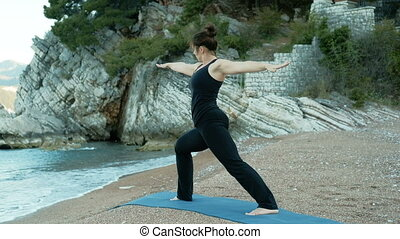 Woman performs pose of warrior in yoga against background of sea rocks
