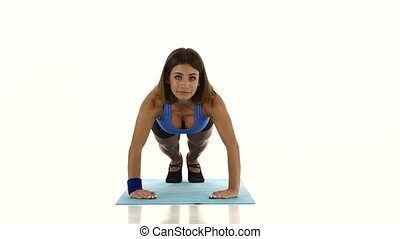 Woman performs pushups on the floor in the room. White
