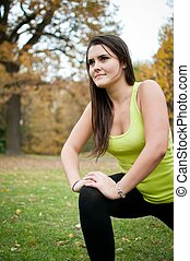 Woman performs stretching before jogging
