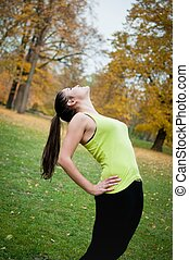 Woman performs stretching before sport outside