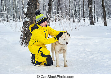 woman petting a husky dog in the winter forest