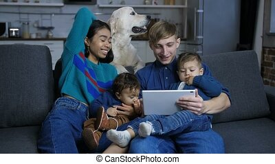 Woman petting dog while family relaxing on sofa - Attracive...