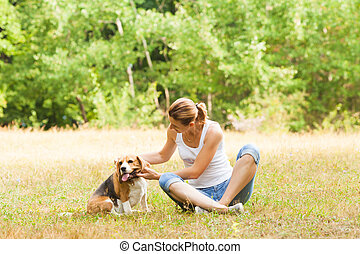 Woman petting her dog outdoors sitting on grass
