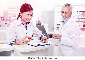 Woman pharmacist checking medicine in a list