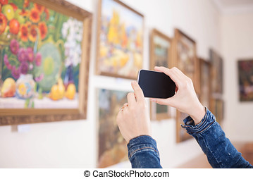 Woman photograph a painting at an exhibition in the art...