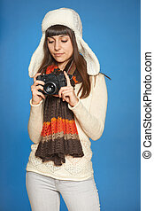 Woman photographer adjusting photo camera settings