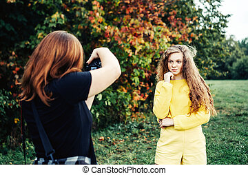 Woman photographer photographing a teenager girl with long red curly hair