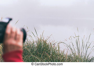 Woman photographer photographs fog on the lake