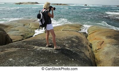 Waterfall Beach in Denmark - Woman photographer pointing her...