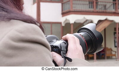 Woman photographer takes pictures in the city