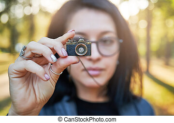Woman photographer, taking pictures on her jewelry camera at sunset