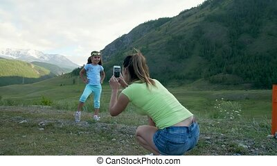 Woman photographing a child on the background of a beautiful landscape of the mountains. Slow motion 4k 60fps. Girl posing for a photo in front of the camera smartphone.