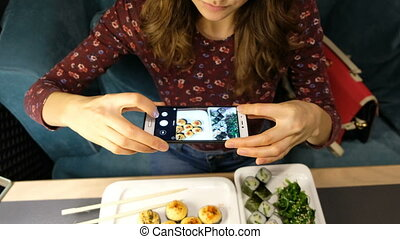 Woman photographing food served in sushi bar with mobile phone. Food and drink concept