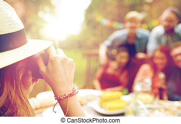 woman photographing friends at summer garden party -...