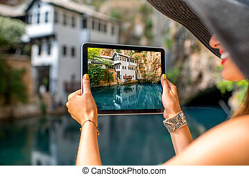 Woman photographing house on Buna spring in Blagaj village -...