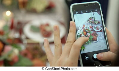 Woman photographing on phone floral fruit composition on...