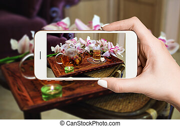 Woman photographing on smartphone, green tea set tray