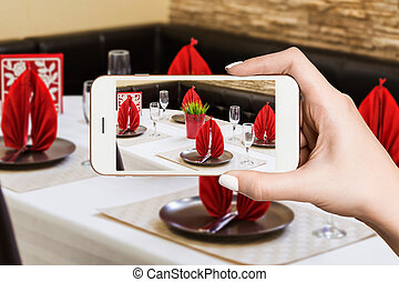 Woman photographing on smartphone, interior of modern restaurant