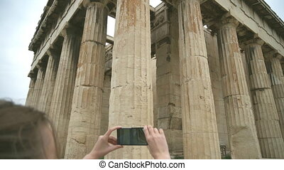Woman photographing Temple of Hephaestus in Athens, Greece.