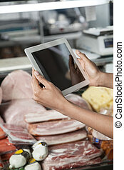 Woman Photographing Through Tablet Computer In Cheese Shop