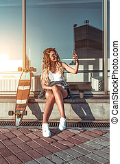 woman photographs herself on phone, takes selfie smartphone, sits city summer window, smiles happy, video recording online Internet call. Skateboard, relaxation after sport fitness, workout.