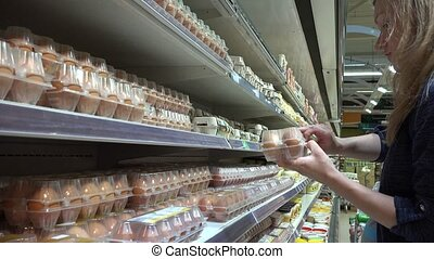 Woman picking eggs in supermarket