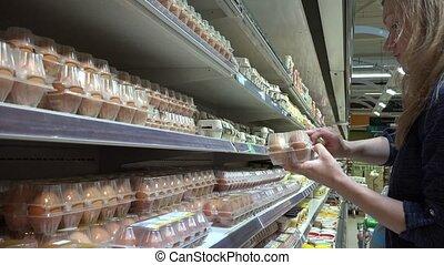 Woman picking eggs in supermarket. Handheld shot