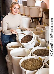 Smiling young woman picking various seeds for birds in shop.