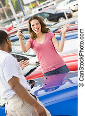 Woman picking up keys to new car