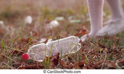 Woman picking up plastic bottle