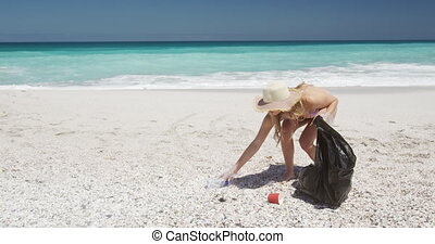 Woman picking up rubbish on the beach and putting it into ...