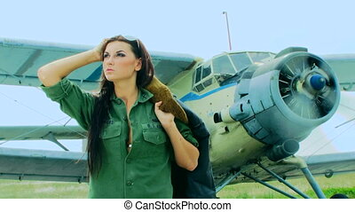 Woman pilot posing in front of a plane